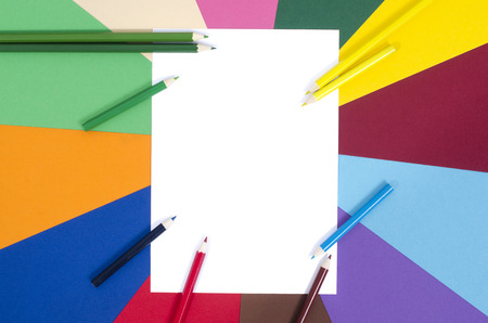 color pencils and white sheet paper all colors pencils arranged around a blank white paper