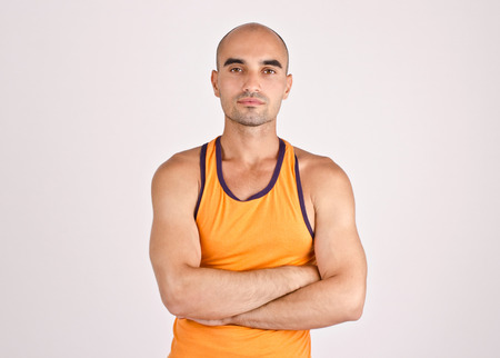 c6f2ef8e35  39141080 - Portrait of a muscular man. Fit athletic man in orange tank  top. Handsome bald man with arms crossed.