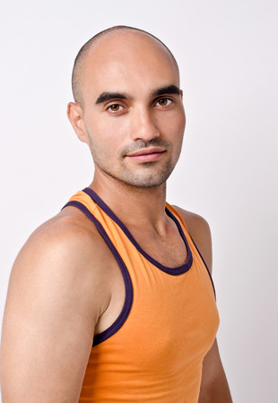 un healthy: Portrait of a man. Profile of a handsome bald man. Fit athletic man in orange tank top.