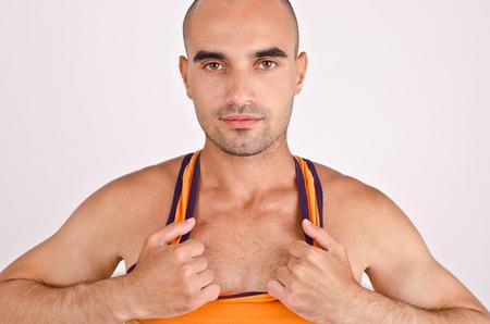 un healthy: Athletic man pulling his orange tank top. Fit handsome bald Caucasian man.