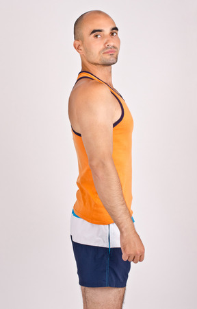 un healthy: Portrait of a man. Profile of a handsome bald man. Fit athletic man wearing an orange tank top. Stock Photo