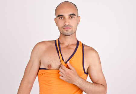 tank top: Athletic man pulling his orange tank top. Fit handsome bald Caucasian man.