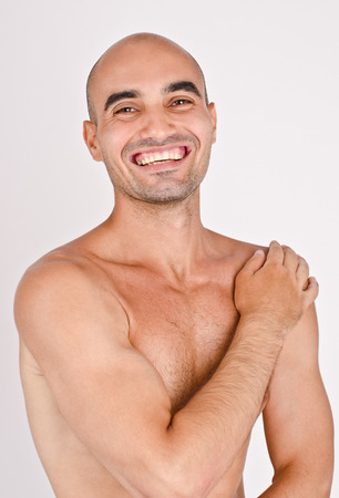 Topless fit Caucasian bald man laughing. Athletic man posing with the arm on the shoulder. photo