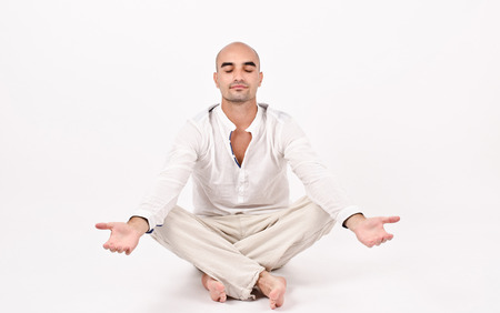 un healthy: Man dressed in white doing yoga.