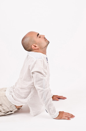 un healthy: Man dressed in white relaxing doing yoga and stretching. Stock Photo