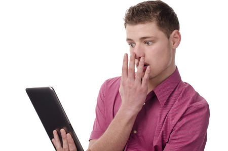 reacting: Man holding a tablet and reacting amazed and surprised Isolated on white.