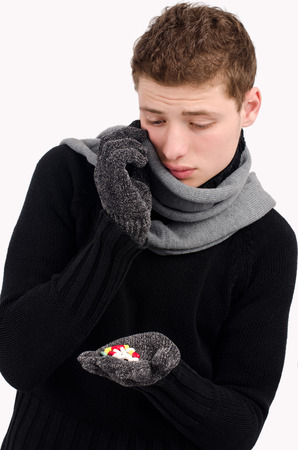Young man feeling sick and cold taking pills. photo