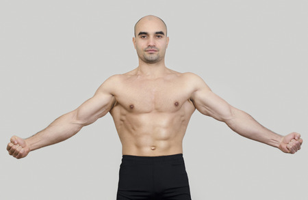 spreading arms: Fit man spreading arms showing his body. Strong bodybuilder man with perfect abs, shoulders,biceps, triceps and chest flexing his muscles. Stock Photo