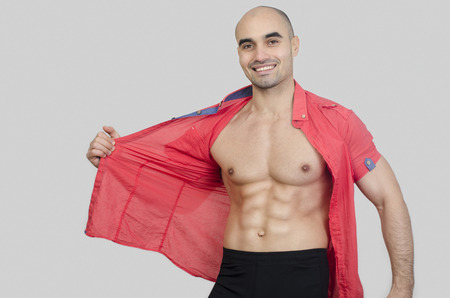 Man smiling showing abs. Happy man puling his shirt showing six pack abdominal.