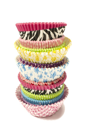 Pile of all colors cupcake paper cups. Stack of colorful muffins liners isolated on white. photo