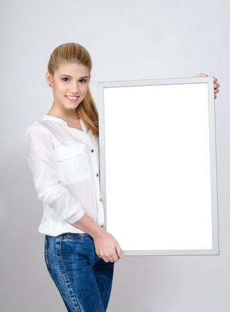 near side: Young girl smiling and holding a white blank board. Beautiful young blonde girl in white shirt. Stock Photo