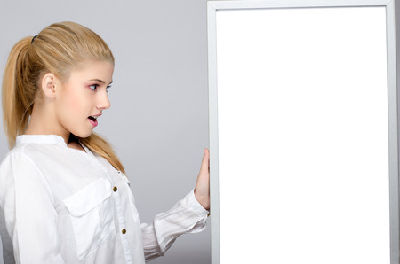 near side: Young girl looking surprised standing near a white board. Young student amazed. Blank white board to write on.