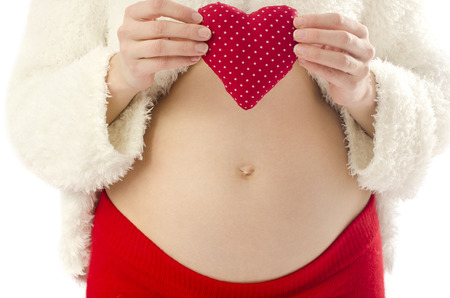 Close up on pregnant belly. Woman expecting a baby holding a red heart with love. photo