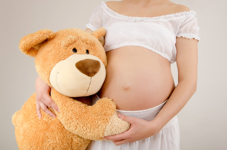 beautiful womb: Close up on pregnant belly and a big teddy bear. Woman expecting a baby with a cute teddy bear huging her belly.