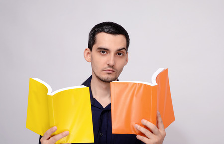 raised eyebrow: Teacher looking amazed at the books raising his eyebrow with suspicion. Surprised student. Man holding two books with orange and yellow blank covers. Stock Photo