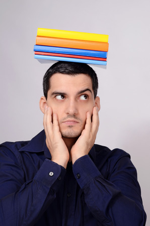 raised eyebrow: Suspicious student holding a pile of books on his head raising his eyebrow. Funny teacher with colorful books over his head looking to the side wondering. Stock Photo