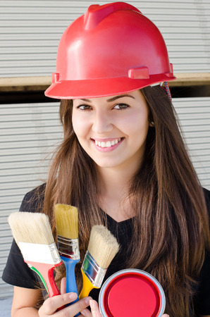 female architect: Beautiful girl wearing a red safety helmet, painter holding brushes and a can of red paint Construction site background.