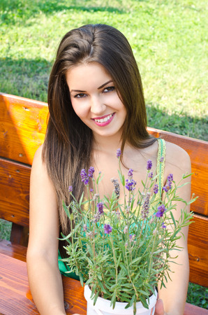 Beautiful woman in the garden sitting on a bench. Girl smiling holding a bouquet of lavender on a hot summer day. photo