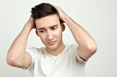 desperation: Desperation, sadness, pressure. Young man holding his head in desperation. Man with different facial expressions.