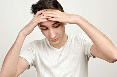 eyes looking down: Stress, sadness, worry. Young man looking down holding his head. Man with different facial expressions.