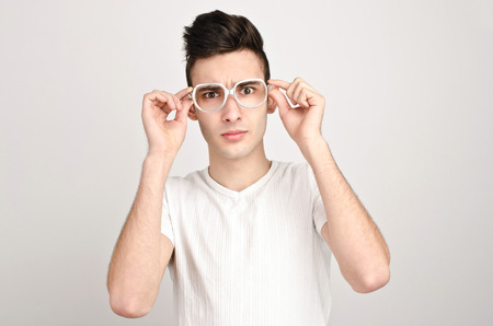 confused man: Confused, disturbed, upset. Young man with funny glasses frowning.
