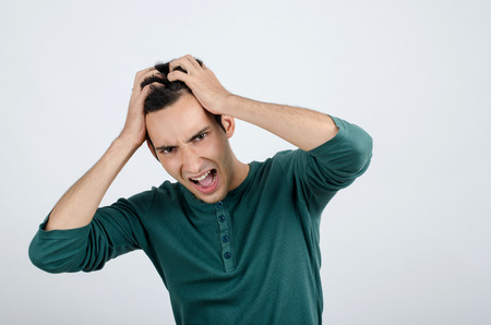 desperation: Young man holding his head frowning with worry screaming. Man pulling his hear for worry, sadness, desperation. Man with different facial expressions.