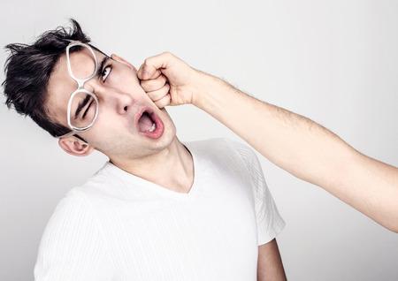 Jeune homme se coup de poing dans la mâchoire. Main d'un homme frappant au visage autre homme. Violence et Bulling. Banque d'images - 44222482