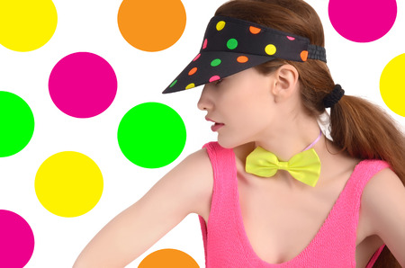 polka dotted: Profile of a young woman wearing a colorful polka dotted hat and a neon green bowtie. Girl hiding behind the cap. Fashion style. Background with dots.