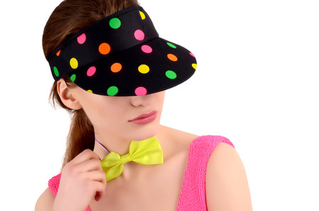polka dotted: Portrait of a young woman wearing a colorful polka dotted hat and a neon green bowtie. Girl hiding behind the cap. Fashion style.