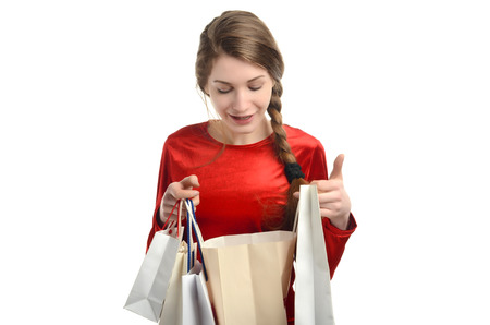 or spree: Young woman looking inside the shopping bags.Girl happy about the gift. Isolated on white. Stock Photo