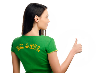 Thumbs up for Brazil. Attractive girl with Brazil written on her green tshirt. Isolated on white. photo