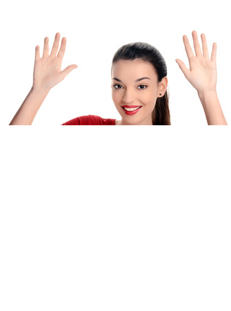 10: Portrait of a beautiful happy woman raising her hands. Behind a white blank poster. Isolated on white background.