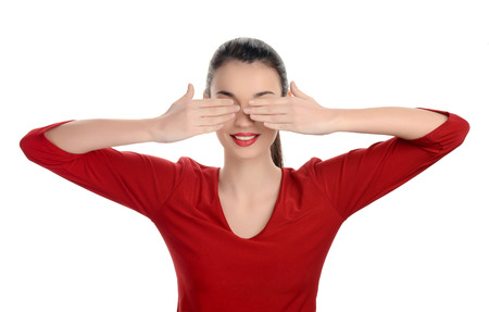 Portrait of a happy young beautiful woman with her hands up covering her eyes. Isolated on white background.