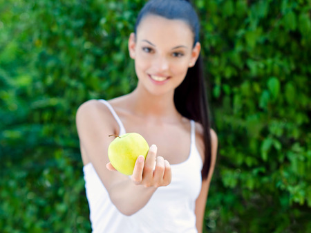 women s health: Beautiful girl offering a yellow apple.Beautiful girl offering a delicious yellow apple outdoors.