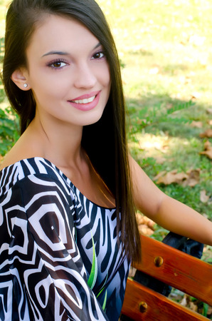 hot girl: Girl smiling sitting on a bench in the park. Portrait of a beautiful woman relaxing in the garden on a hot summer day.