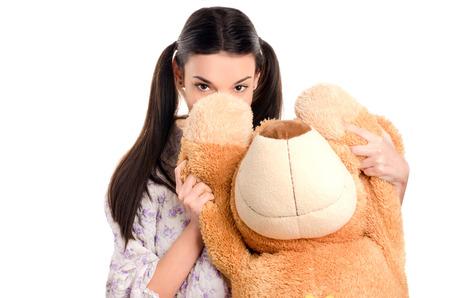 big behind: Girl hiding behind the big teddy bear. Piercing beautiful eyes looking over the cute teddy bear. Stock Photo