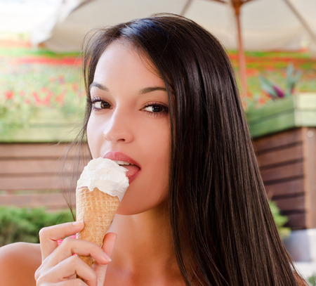 ice cream woman: Beautiful woman eating a delicious ice cream. Girl sitting at a terrace on a hot day eating a delicious vanilla chocolate ice cream. Stock Photo
