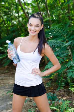 Beautiful girl laughing holding a bottle of water after sports, outdoors photo