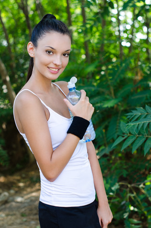 Beautiful girl smiling holding a bottle of water after sports, outdoors photo