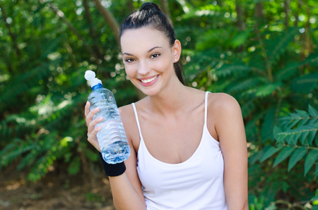 Beautiful girl laughing holding a bottle of water after sports, outdoors. photo