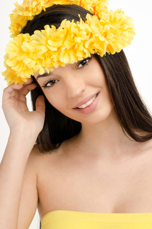 ringlet: Portrait of a sexy woman with wreath of yellow flowers. Beautiful smiling brunette woman wearing a ringlet of flowers.