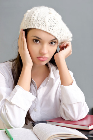 Bored student girl. Beautiful brunette girl exhausted and unhappy from all the studying. photo
