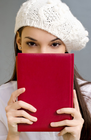 Piercing eyes looking over a notebook. Beautiful student girl holding a notebook. Dressed in white wearing a beret. photo