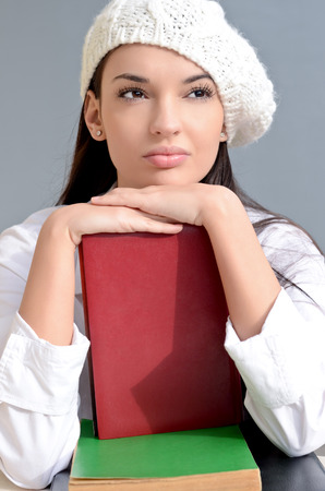 Beautiful student girl with books. Beautiful brunette student girl thinking. Dressed in white wearing a beret. photo