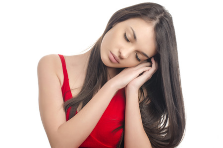 wanting: Sexy girl in red dress sleeping. Gorgeous woman with long brunette hair wearing a sexy red dress being tired wanting to take a nap. Isolated on white background. Stock Photo