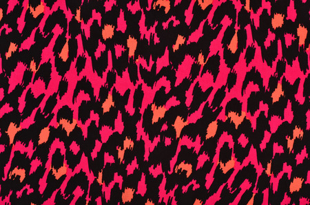 Pink and orange leopard fur pattern.  Colorful magenta spotted animal print as background.
