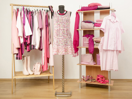 ropa de verano: Armario lleno de todos los tonos de ropa de color rosa, zapatos y accesorios. Foto de archivo