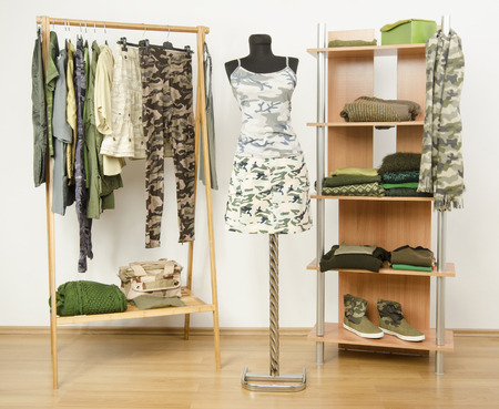 green clothes: Dressing closet with military camouflage khaki green clothes arranged on hangers and shelf, outfit on a mannequin.