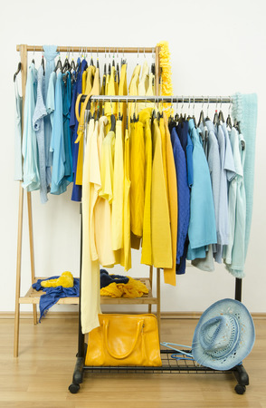 clothes rack: Wardrobe with shades of yellow and blue clothes hanging on a rack nicely arranged. Color coordinated clothes on hangers in a store. Stock Photo