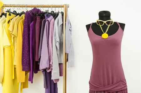 complementary: Dressing closet with complementary colors violet and yellow clothes. Wardrobe with purple and yellow clothes arranged on hangers and a summer dress on a mannequin.